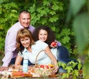 Familia joven feliz en comida campestre del otoño Imagenes de archivo