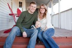 Familia joven feliz en el pórtico Foto de archivo libre de regalías