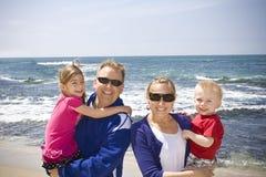Familia joven feliz en la playa Foto de archivo libre de regalías