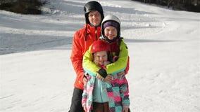 Familia joven feliz en Ski Suit With Funny Children en ropa brillante del invierno El caminar llevando a cabo las manos en parque almacen de video