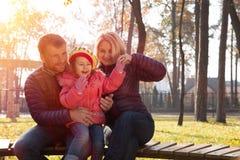 Familia joven feliz junto en la risa del parque Foto de archivo libre de regalías