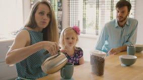 Familia joven feliz: mamá, papá y su hija desayunando en la tabla de cocina Cámara lenta almacen de metraje de vídeo