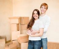 Familia joven feliz que abraza en un fondo de las cajas de cartón Fotos de archivo libres de regalías