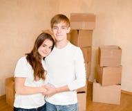 Familia joven feliz que abraza en un fondo de las cajas de cartón Fotografía de archivo