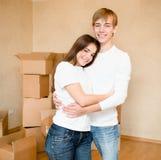 Familia joven feliz que abraza en un fondo de las cajas de cartón Foto de archivo libre de regalías