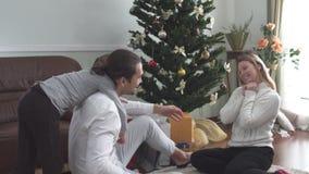 Familia joven feliz que abraza la sentada en el piso por el árbol de navidad Padres y niño alegres metrajes