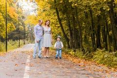 Familia joven feliz que camina abajo del camino afuera en naturaleza del otoño Foto de archivo