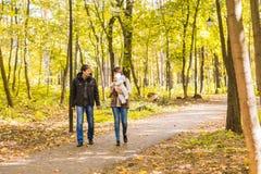Familia joven feliz que camina abajo del camino afuera en naturaleza del otoño Fotos de archivo libres de regalías