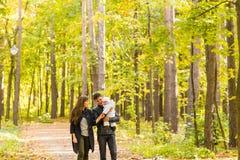 Familia joven feliz que camina abajo del camino afuera en naturaleza del otoño Imagenes de archivo