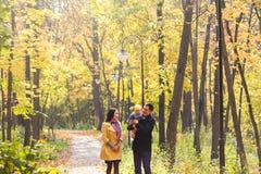 Familia joven feliz que camina abajo del camino afuera en naturaleza del otoño Imagen de archivo