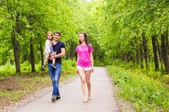 Familia joven feliz que camina abajo del camino afuera en naturaleza verde Imagenes de archivo