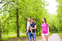 Familia joven feliz que camina abajo del camino afuera en naturaleza verde Fotografía de archivo libre de regalías