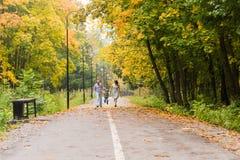 Familia joven feliz que camina abajo del camino afuera en naturaleza verde Imagen de archivo