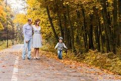 Familia joven feliz que camina abajo del camino afuera en naturaleza verde Fotos de archivo libres de regalías
