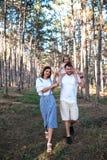 Familia joven feliz que camina en el bosque imagen de archivo