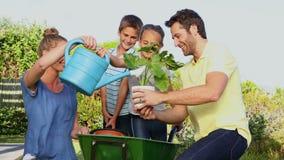 Familia joven feliz que cultiva un huerto junto almacen de video