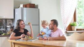 Familia joven feliz que desayuna en la cocina Comida nutritiva metrajes