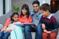 Familia joven feliz que lee un libro junto Fotografía de archivo