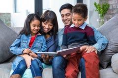 Familia joven feliz que lee un libro junto Imagen de archivo