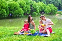 Familia joven feliz que merienda en el campo al aire libre Imágenes de archivo libres de regalías