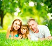 Familia joven feliz que miente en hierba verde Fotos de archivo