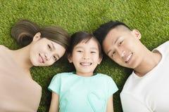 Familia joven feliz que miente en la hierba Imagen de archivo libre de regalías
