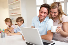 Familia joven feliz que mira y que lee una computadora portátil Imagen de archivo libre de regalías