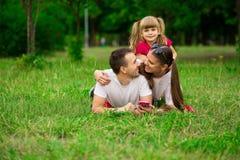 Familia joven feliz que pasa el tiempo al aire libre el día de verano Felicidad y armonía en vida familiar Fotos de archivo