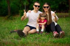 Familia joven feliz que pasa el tiempo al aire libre el día de verano Felicidad y armonía en vida familiar Fotografía de archivo