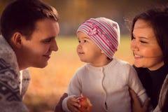 Familia joven feliz que pasa el tiempo al aire libre en el parque del otoño Imagen de archivo