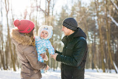 Familia joven feliz que pasa el tiempo al aire libre en invierno Imagen de archivo libre de regalías