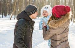 Familia joven feliz que pasa el tiempo al aire libre en invierno Foto de archivo
