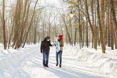Familia joven feliz que pasa el tiempo al aire libre en invierno Imagenes de archivo