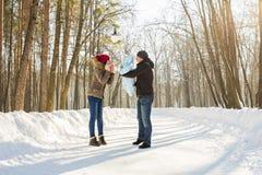 Familia joven feliz que pasa el tiempo al aire libre en invierno Fotografía de archivo libre de regalías