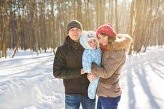 Familia joven feliz que pasa el tiempo al aire libre en invierno Fotos de archivo libres de regalías
