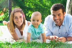 Familia joven feliz que pasa el tiempo al aire libre en un daycouple del verano fotos de archivo