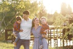 Familia joven feliz que pasa el tiempo junto afuera en naturaleza verde Padres que juegan con los gemelos afuera fotos de archivo