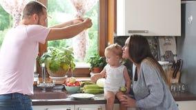 Familia joven feliz que prepara el desayuno en la cocina metrajes