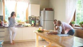 Familia joven feliz que prepara el desayuno en la cocina almacen de video