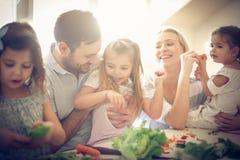 Familia joven feliz que prepara la ensalada junta imagen de archivo