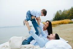 Familia joven feliz que se relaja junto en el lago imagen de archivo libre de regalías