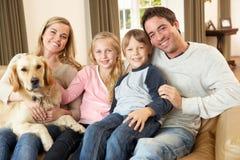 Familia joven feliz que se sienta en el sofá que sostiene un perro Imágenes de archivo libres de regalías