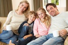 Familia joven feliz que se sienta en las tazas de la explotación agrícola del sofá Imagen de archivo