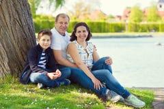 Familia joven feliz que se sienta en parque en hierba y hablar Fotos de archivo libres de regalías