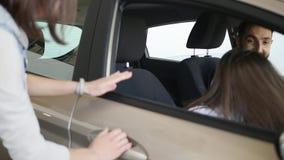 Familia joven feliz que se sienta en un nuevo coche junto en la representación almacen de metraje de vídeo