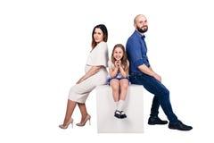 Familia joven feliz que se sienta en un pedestal contra el fondo blanco fotos de archivo