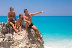 Familia joven feliz que se sienta en una roca en la playa que mira el som fotos de archivo