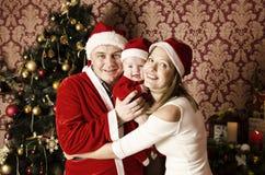 Familia joven hermosa con el pequeño bebé lindo en la Navidad Imagenes de archivo