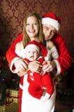 Familia joven hermosa con el pequeño bebé lindo en la Navidad Fotos de archivo
