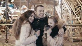 Familia joven hermosa en un parque de atracciones encendido contra un carrusel metrajes